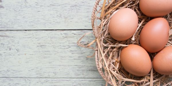 fresh local eggs in basket on rustic tabletop