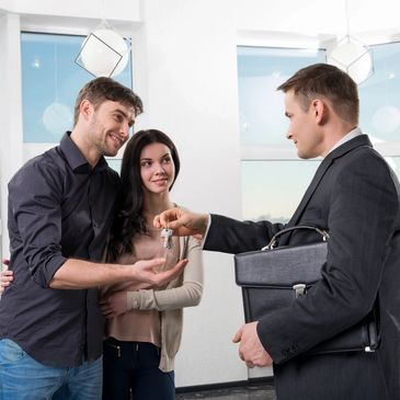 Real estate agent handing keys to the new homeowners