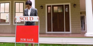 Realtor® placing SOLD sign in front of home.