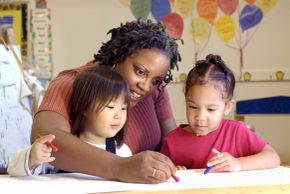 Teacher helping two toddlers in a kindergarten activity. Signifies learning more about something.