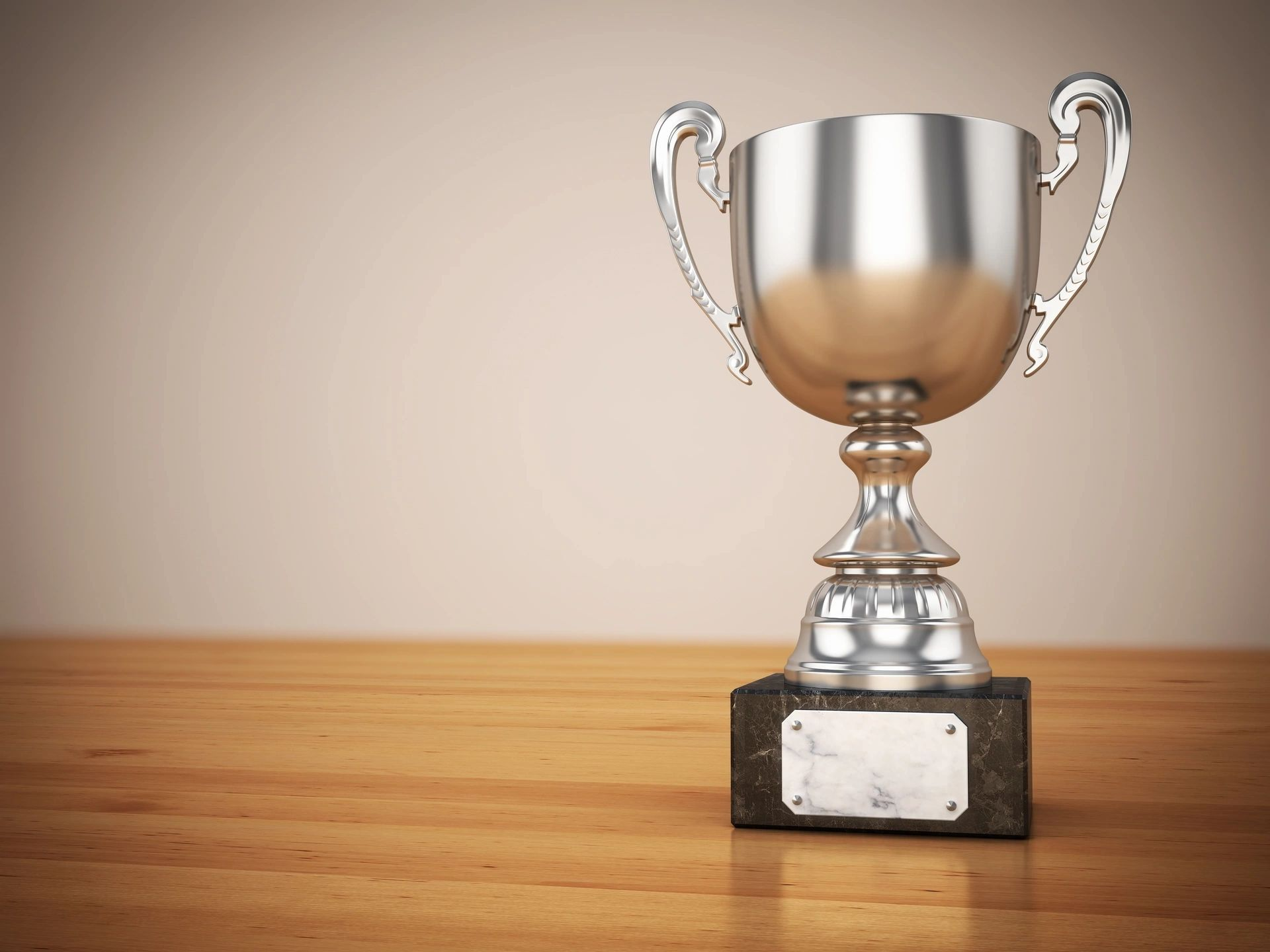 Silver trophy cup on woodgrain desktop