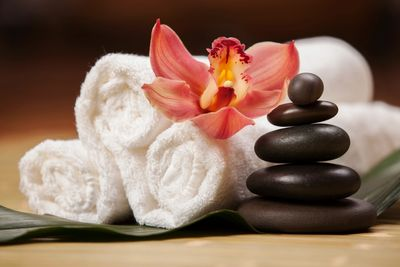 Three rolled up white towels with brown spa stones and orchid flower.