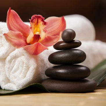 Rolled towels, an orchid flower and a stack of hot stones for massage