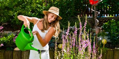 Woman wearing hat watering her flowers with a green water can