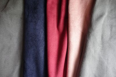 Grey, blue, red, gold and silver fabric on display