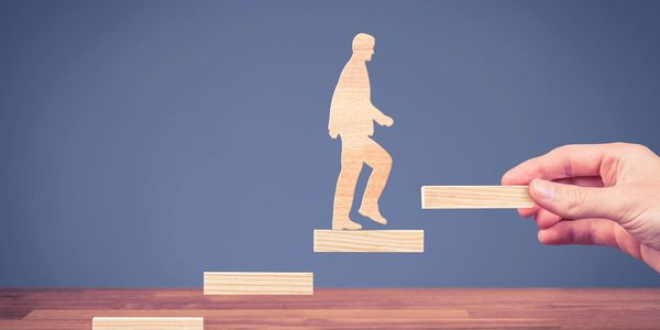 An image of a man walking up a floating staircase in the form of animation.