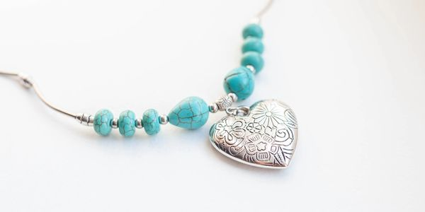 A heart necklace with turquoise beads.