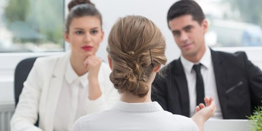 image of an interview. two individuals in business wear face a third individual, seen from the back.