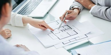 Two people at a desk reviewing floorplans.