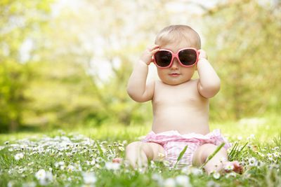 baby wearing only diaper and sunglasses sitting in a field of flowers