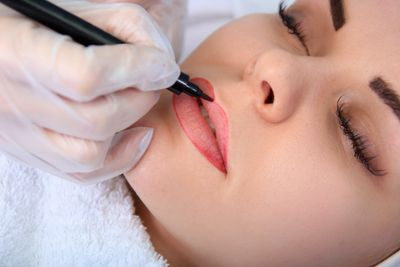 Graceful Glamour cosmetologist applies permanent lip makeup, lip tattoo, permanent lip coloring