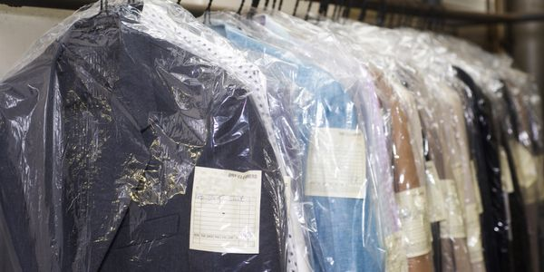 dry cleaners, bagged and tagged clothing, clean suits, cleaners, suits , dresses, clothing on a rack