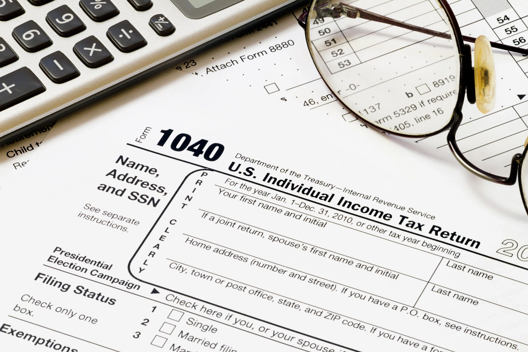 Picture of Form 1040 U.S. Individual; Tax service, Tax Preparer, Tax Practitioner, Virtual Tax Office, Online Tax Service, Online Tax Office Income Tax Return and eyeglasses for reading tax preparation documents.