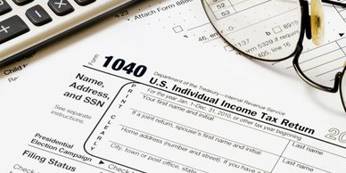 Individual income tax form, calculator and glasses