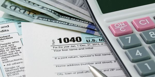 Tax material including a 1040 form, a calculator and some money.