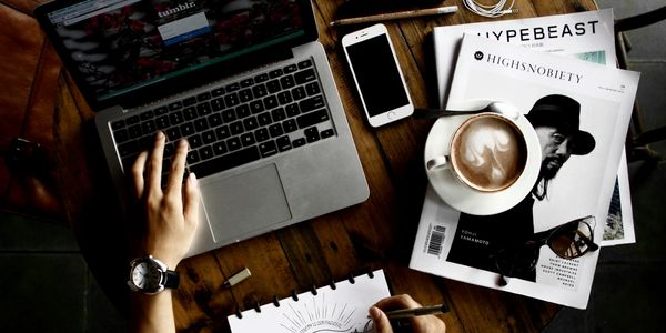 A designer with a laptop, coffee and some books on the table.