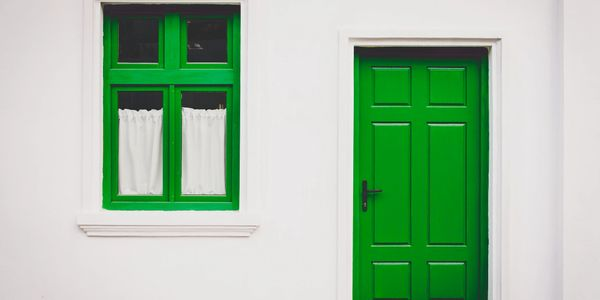 Striking green door and matching window trim on clean white house.