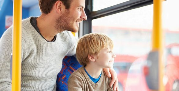 picture of a dad with his son looking out a window of a bus.