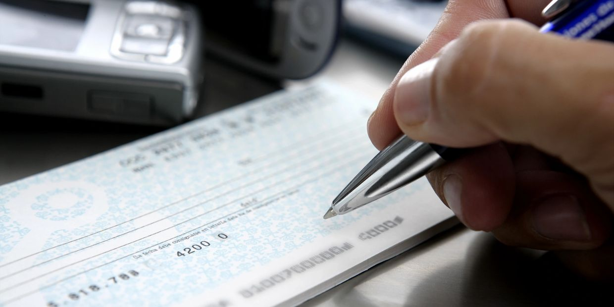 man woman writing a check for a payday loan cash advance cashing payroll check