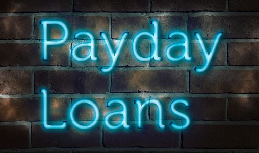 payd day loan blue neon sign on brick wall storefront cash advance building sign