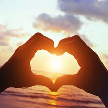 heart hand sign with sunrise background