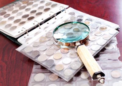 coin collections and old collectible coins inside plastic page holders on table with magnifier