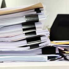 a stack of paper files on a desk ready to be scanned
