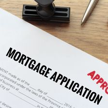 A Mortgage Application on a wooden table that has been stamped APPROVED.