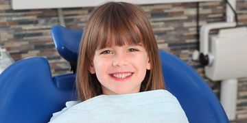 Photo of a smiling girl in a dentist chair with a green dental bib, ready for a dental check-up.