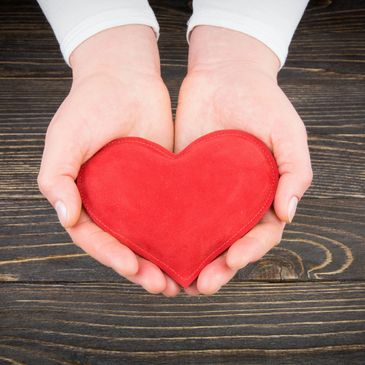 Red heart held by two hands, SLC Group Holdings -  Philanthropic Efforts