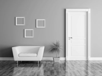 Three empty frames on a wall with a chair, plant and door.
