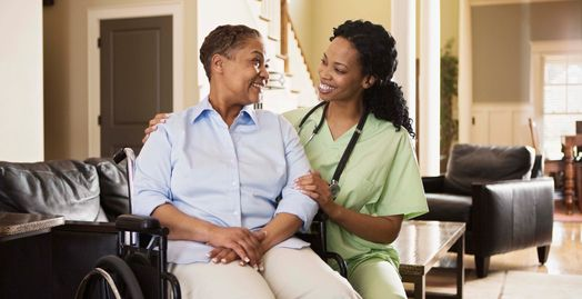 Woman PCA nurse and woman in wheelchair smiling at each other