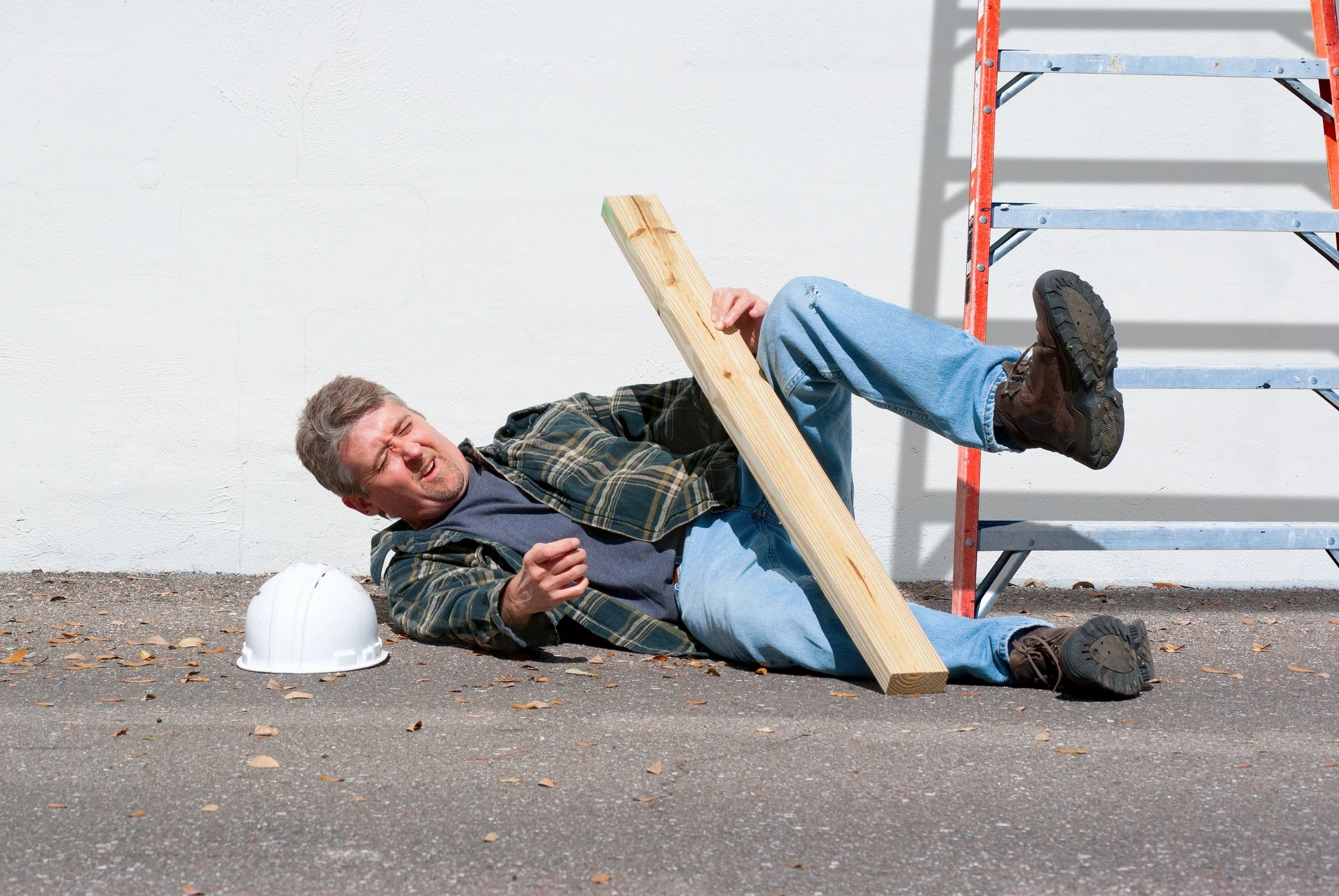 a working man in boots laying on the ground after falling from a ladder and getting injured