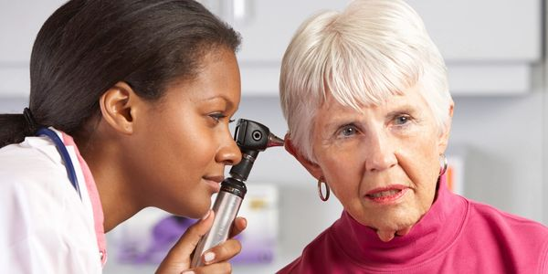 Audiologist examining a patients ears