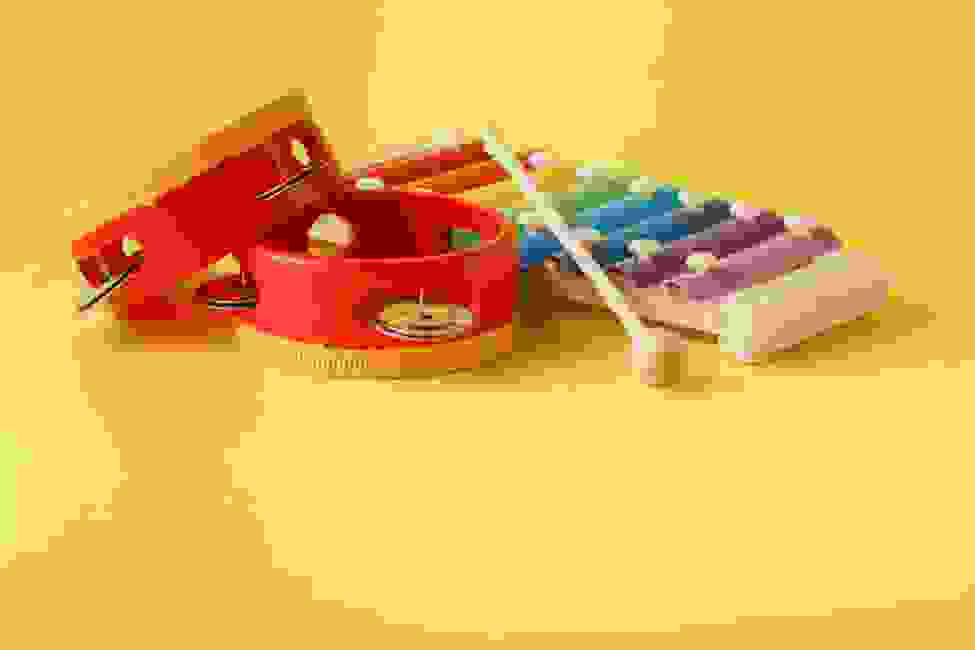 A toy Xylophone and two red tambourines ready for music with infants.