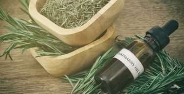 a wooden bowl of dried rosemary sitting on a bowl of fresh rosemary branches beside a small pile of rosemary branches where an glass bottle with a black dropper top rests