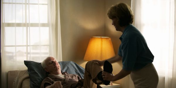 A Mercy Works Louisville caregiver assist a client with stretching.  We provide assistance in home!