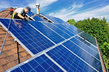 Man installing solar panels on a residential rooftop with trees and shade in the background