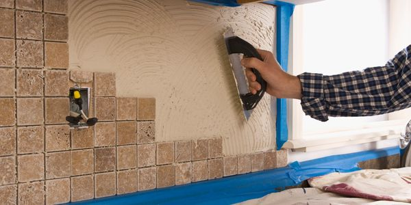 Worker tiling a wall