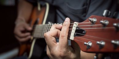 Hands playing an acoustic guitar.