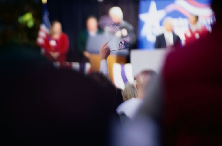 Blurred picture from the audience, point of view. looking at political candidates on stage, lots of