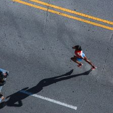 A woman is jogging on a road, image is from a helicopter view. It may be part of  a sports event.
