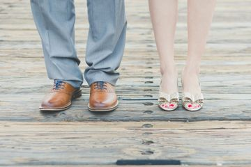 bridal shoes and groom's shoes on wooden floor
