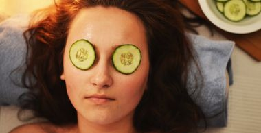 The face of a lady that is lying on a rolled towel with cucumber slices on her eyes.  A bowl of cucumbers is in the background.
