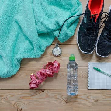 fitness still life with towel, running shoes, tape measure, stop watch, water bottle and notepad.