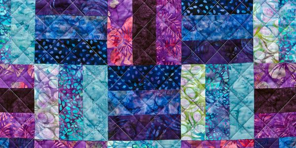 A colourful patchwork piece, with cross hatch quilting