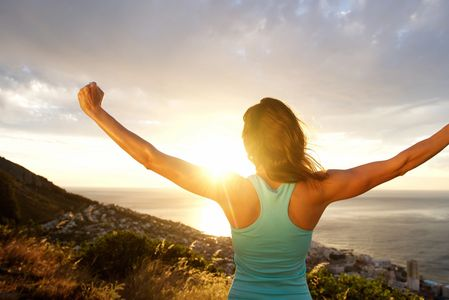 woman raising her arms in triumph on a cliff overlooking the ocean at sunset