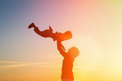 Parent lifting up a child in the air.  Single parent.  Young Child.  Protecting children and parents