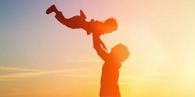 Silhouette of an adult playfully throwing a child in the air