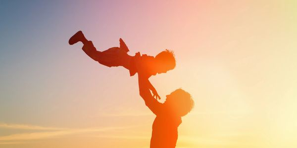 For screen readers: an image of an adult holding a child above them at sunset